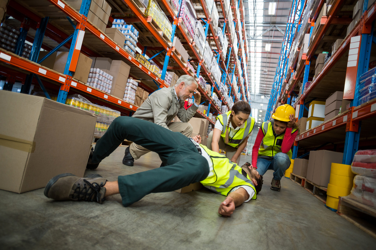 Worker fallen down while carrying cardboard boxes in warehouse